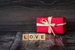 O presente na caixa vermelha e a palavra amam, alinhado com blocos de madeira, na Dinamarca Fotografia de Stock