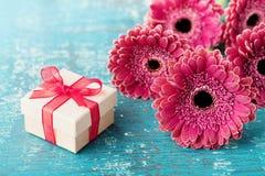 O presente ou a caixa atual para o dia da mãe ou da mulher decorado com a margarida bonita do gerbera florescem no fundo de madei Fotos de Stock