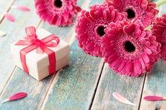 O presente ou o presente para o dia da mãe ou da mulher decorado com a margarida bonita do gerbera florescem no fundo do vintage Imagem de Stock Royalty Free