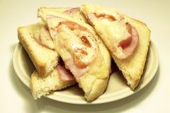 O presunto, os tomates e os triângulos do brinde do queijo serviram em uma placa imagens de stock royalty free