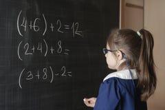 O primeiro-graduador italiano da menina da escola primária resolve a matemática Imagem de Stock