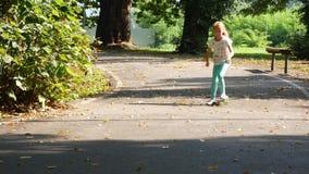 O primeiro tenta em skateboarding Menina que empurra um pé contra a terra vídeos de arquivo
