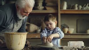 O principiantes novo diligente está dando forma ao potenciômetro de argila sob a orientação de seu professor masculino experiente