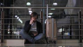 O problema com transporte, atraso do voo, o homem deprimido sua bagagem e a tabuleta, vermelho da dor de cabeça eyes Imagens de Stock Royalty Free