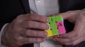 O problema e resolve O homem de negócios entrega a resolução do enigma do cubo do ` s de Rubik video estoque