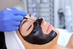 O procedimento para aplicar uma máscara preta à cara de uma mulher bonita foto de stock royalty free