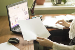 O processo com de um portátil e de originais em uma mesa de escritório imagem de stock royalty free