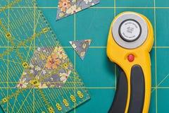O processo de cortar partes de tela na forma dos hexágonos para criar um processo do quiltThe de cortar partes de tela no s fotos de stock