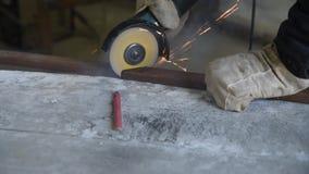 O processo de cortar o perfil retangular do metal usando o moedor de ângulo bonde, faíscas voa ao redor, habilidade do especialis filme