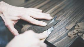 O processo de cortar um couro com uma faca Fotografia de Stock Royalty Free