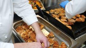 O processo de cozimento na cozinha do restaurante, o cozinheiro chefe prepara os bifes conservados na grade his video estoque
