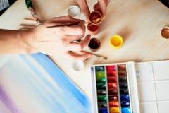 O processo de criar uma ilustração pela pintura de Watercolor do artista Mão com escova imagem de stock royalty free