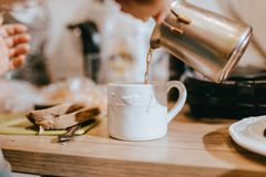O processo de derramar o café dos turcos em um copo branco bonito na cozinha em uma tabela de madeira fotos de stock royalty free