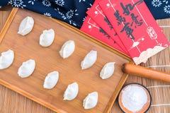 O processo de fazer dumplingsDumplings, farinha, varas de rolamento, envelopes vermelhos na tabela de madeira fotos de stock