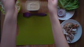 O processo de fazer o shawarma com mãos fêmeas em uma tabela de madeira, vista superior video estoque
