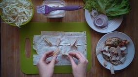 O processo de fazer o shawarma com mãos fêmeas em uma tabela de madeira, vista superior vídeos de arquivo