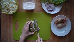 O processo de fazer o shawarma com mãos fêmeas em uma tabela de madeira, vista superior filme