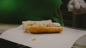 O processo de fazer um sanduíche grande da carne da galinha, as mãos humanas apresenta ingredientes na grande parte do pão com video estoque