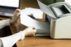 O processo de introduzir o papel no cartucho de impressora a laser fotografia de stock