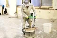 O processo de misturar a mistura da massa de vidraceiro para a construção imagem de stock