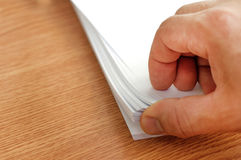 O processo de paginar o papel branco do escritório com seus dedos Fotografia de Stock Royalty Free