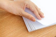 O processo de paginar o papel branco do escritório com seus dedos Imagens de Stock