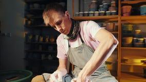 O processo de trabalho do trabalho do homem em oleiro roda no estúdio da arte O artesão novo caucasiano cria o jarro Foco nas mão vídeos de arquivo