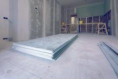 O processo de trabalho de instalar quadros do metal e drywall da placa de gesso e os materiais no apartamento estão sob a constru imagem de stock