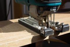 O processo de ver uma placa de madeira com uma serra de vaivém pelo trabalhador manual fotos de stock royalty free