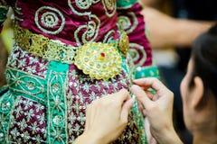 O processo de vestir a pantomima tailandesa para os atores com mão que costuram, reparando foto de stock