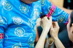 O processo de vestir a pantomima tailandesa para os atores com mão que costuram, reparando imagens de stock royalty free