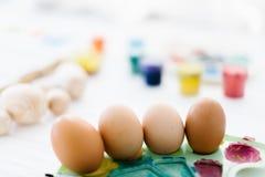 O processo de vida dos ovos da páscoa da pintura ainda em um fundo de madeira branco Imagens de Stock Royalty Free