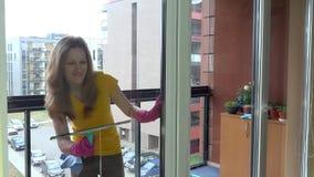 O produto químico do pulverizador do trabalhador fêmea e a janela bonitos da limpeza em clientes dirigem vídeos de arquivo