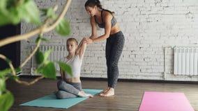 O professor alegre da ioga está ajudando a vaca nova do mestre do estudante a enfrentar a pose durante a classe linear no centro  filme