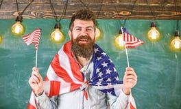 O professor americano acena com bandeiras americanas Conceito patri?tico da educa??o Programa da troca do estudante Homem com bar foto de stock