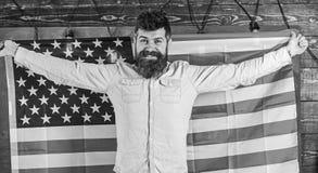 O professor americano guarda a bandeira americana O homem com barba e bigode na cara feliz guarda a bandeira dos EUA, fundo de ma fotos de stock