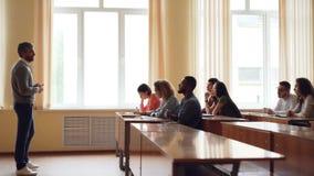 O professor amigável está falando aos estudantes, o homem esperto da raça misturada está levantando a mão e o assento falador na  vídeos de arquivo