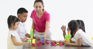 O professor asiático deixa os estudantes asiáticos que jogam blocos de madeira coloridos brinca junto, conceito para a sala de au filme