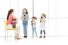 O professor asiático está ensinando crianças cantar fotografia de stock