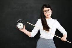 O professor asiático está muito irritado para um estudante que sempre tarde imagens de stock