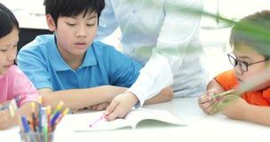 O professor asiático novo ajuda crianças novas da escola na classe, fim acima vídeos de arquivo