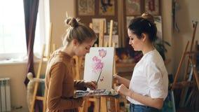 O professor bonito da pintura da mulher está ensinando a moça misturar pinturas na paleta que cria a cor bonita durante a classe  video estoque