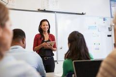O professor com tabuleta e os estudantes em um ensino para adultos classificam imagens de stock