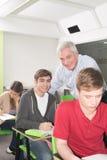 O professor da faculdade ajuda seus estudantes foto de stock