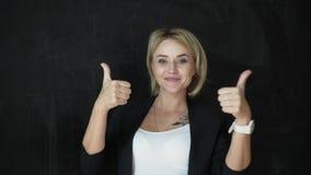 O professor de sorriso está mostrando seu polegar que aponta acima o gráfico video estoque