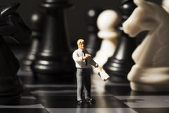 O professor diminuto explica regras do jogo de xadrez a bordo Conceito da análise da estratégia da xadrez fotos de stock
