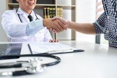 O professor Doctor que tem a agitação das mãos com o paciente após recomenda o método de tratamento ao discutir explicando seus s imagem de stock