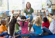 O professor e as crianças com mãos levantaram na biblioteca Imagens de Stock Royalty Free