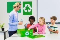 O professor e as crianças que discutem reciclam aproximadamente foto de stock