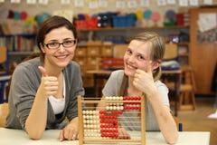 O professor e um estudante mostram nos polegares da escola acima Imagens de Stock Royalty Free